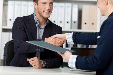Happy businessman shaking hands with a female interviewer in office-1